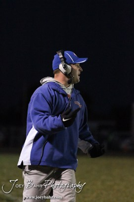 Otis-Bison Cougar Head Coach Travis Starr talks to a player after a play during the Sylvan-Lucas vs Otis-Bison High School football game with Otis-Bison winning 32 to 30 at Otis-Bison High School Field in Otis, Kansas on October 31, 2013. (Photo: Joey Bahr, www.joeybahr.com)