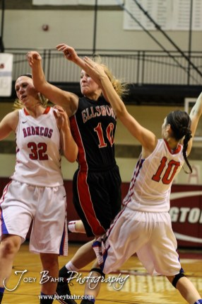 Ellsworth Lady Bearcat Halle Connally (#10) goes through the defense of Russell Lady Broncos Janna Schulte (#32) and Lena Wedel (#10) during the 2014 Hoisington Cardinal Winter Jam First Round basketball game with the Russell Lady Broncos versus the Ellsworth Lady Bearcats with Russell winning 54 to 52 in Hoisington Activity Center in Hoisington, Kansas on January 20, 2014. (Photo: Joey Bahr, www.joeybahr.com)