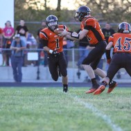 Larned Indian Trey Kraisinger (#11) fakes a handoff to Evan Skelton (#1) during the Kingman Eagles versus Larned Indians High School Football Game with Kingman winning 3 to 0 at Earl Roberts Field at Larned High School near Larned, Kansas on September 19, 2014. (Photo: Joey Bahr, www.joeybahr.com)
