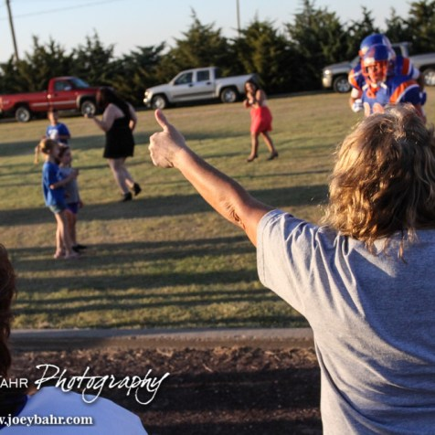 A fan cheers as the Otis-Bison Cougars run to the field before the Otis-Bison versus Kinsley High School 8-Man Football Game with Otis-Bison winning 104 to 70 which set a new state record for combined points in a game at Cougar Field at Otis-Bison High School in Otis, Kansas on September 26, 2014. (Photo: Joey Bahr, www.joeybahr.com)