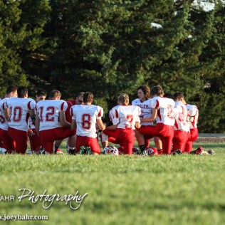 The Kinsley Coyotes kneel to pray before the Otis-Bison versus Kinsley High School 8-Man Football Game with Otis-Bison winning 104 to 70 which set a new state record for combined points in a game at Cougar Field at Otis-Bison High School in Otis, Kansas on September 26, 2014. (Photo: Joey Bahr, www.joeybahr.com)