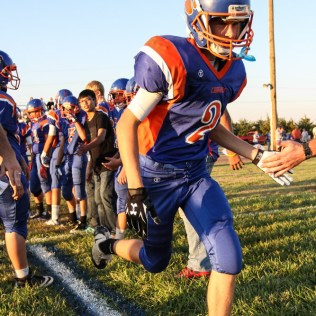 Otis-Bison Cougar Brandon Keller (#2) runs out for player introductions during the Otis-Bison versus Kinsley High School 8-Man Football Game with Otis-Bison winning 104 to 70 which set a new state record for combined points in a game at Cougar Field at Otis-Bison High School in Otis, Kansas on September 26, 2014. (Photo: Joey Bahr, www.joeybahr.com)