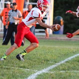 Kinsley Coyote Ross Frame (#5) hands the ball off during the Otis-Bison versus Kinsley High School 8-Man Football Game with Otis-Bison winning 104 to 70 which set a new state record for combined points in a game at Cougar Field at Otis-Bison High School in Otis, Kansas on September 26, 2014. (Photo: Joey Bahr, www.joeybahr.com)