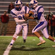 Lyons Lion Tyler Edwards (#15) fakes a handoff to Cody Clarke (#21)during the Hoisington Cardinals versus Lyons Lions High School Football game with Hoisington winning 54 to 13 at Elton Brown Field at Hoisington High School in Hoisington, Kansas on October 30, 2014. (Photo: Joey Bahr, www.joeybahr.com)