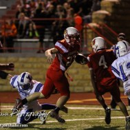 Hoisington Cardinal Hunter Hanzlick (#27) rushes past a Lyons Lion during the Hoisington Cardinals versus Lyons Lions High School Football game with Hoisington winning 54 to 13 at Elton Brown Field at Hoisington High School in Hoisington, Kansas on October 30, 2014. (Photo: Joey Bahr, www.joeybahr.com)