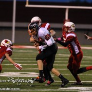 The Hoisington Cardinals swarm to Smoky Valley Viking Cole Norberg (#4) during the Hoisington High School versus Smoky Valley football game with Hoisington winning 33 to 12 at Eldon Brown Field in Hoisington, Kansas on October 10, 2014. (Photo: Joey Bahr, www.joeybahr.com)