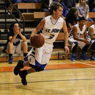 St. John Tiger Quincy Smith (#3) dribbles the ball during the Seventh Annual Keady Basketball Classic First Round game between the St. John Tigers and the Kiowa County Mavericks with St. John winning 74 to 30 at Larned Middle School in Larned, Kansas on December 9, 2014. (Photo: Joey Bahr, www.joeybahr.com)