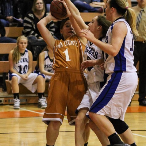 Kiowa County Lady Maverick Morgan Powell (#1) tries to go for a shot as she is challenged by St. John Lady Tiger Torre Fisher (#3) during the Seventh Annual Keady Basketball Classic First Round game between the St. John Lady Tigers and the Kiowa County Lady Mavericks with St. John winning 47 to 31 at Larned Middle School in Larned, Kansas on December 9, 2014. (Photo: Joey Bahr, www.joeybahr.com)