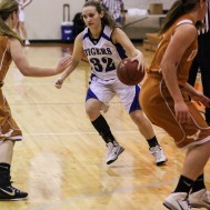 St. John Lady Tiger Brandi Hanson (#32) looks for a hole to dribble through during the Seventh Annual Keady Basketball Classic First Round game between the St. John Lady Tigers and the Kiowa County Lady Mavericks with St. John winning 47 to 31 at Larned Middle School in Larned, Kansas on December 9, 2014. (Photo: Joey Bahr, www.joeybahr.com)