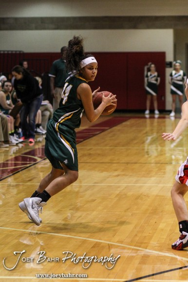 Pratt Lady Greenback Stonie Flemming (#14) looks for someone to pass to during the Pratt Lady Greenbacks at Hoisington Lady Cardinals Girls Basketball game with Pratt winning 34 to 23 at Hoisington Activity Center in Hoisington, Kansas on January 6, 2015. (Photo: Joey Bahr, www.joeybahr.com)
