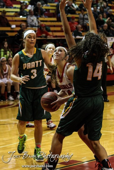 Hoisington Lady Cardinal Lexi Sanders (#24) looks to take a shot as Pratt Lady Greenback Stonie Flemming (#14) defends during the Pratt Lady Greenbacks at Hoisington Lady Cardinals Girls Basketball game with Pratt winning 34 to 23 at Hoisington Activity Center in Hoisington, Kansas on January 6, 2015. (Photo: Joey Bahr, www.joeybahr.com)