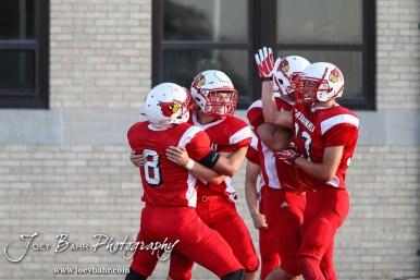 The Hoisington Cardinals celebrate Hunter Hanzlick's (#27) touchdown during the Hoisington Cardinal versus Larned Indian Football game with Hoisington winning 53 to 21 at Elton Brown Field in Hoisington, Kansas on September 4, 2015. (Photo: Joey Bahr, www.joeybahr.com)