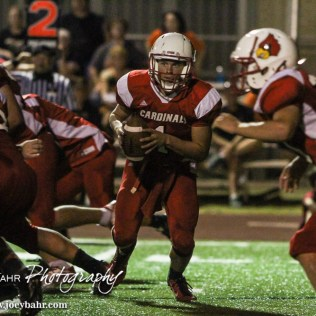 Hoisington Cardinal Tyler Specht (#1) spins to hand off the ball during the Hoisington Cardinal versus Larned Indian Football game with Hoisington winning 53 to 21 at Elton Brown Field in Hoisington, Kansas on September 4, 2015. (Photo: Joey Bahr, www.joeybahr.com)