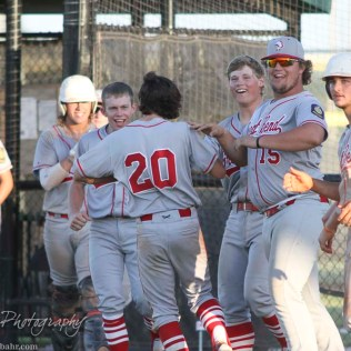 Great Bend Chief Bryce Lytle (#20) scores the winning walk off run and his teammates greet him outside the dugout. The Great Bend Chiefs win game 1 of a American Legion baseball double header over the Larned Indians 7 to 6 after 8 innings at the Great Bend Sports Complex in Great Bend, Kansas on June 29, 2016. (Photo: Joey Bahr, www.joeybahr.com)