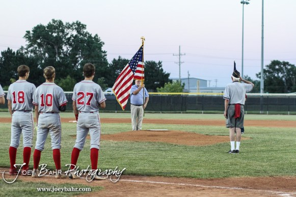 Steve Queen of the American Legion salutes the colors as members of the Great Bend Braves stand for the National Anthem. The Great Bend Braves won their first round game over Doniphan County 14 to 4 in the American Legional Class A Baseball State Tournament at the Great Bend Sports Complex in Great Bend, Kansas on July 20, 2016. (Photo: Joey Bahr, www.joeybahr.com)