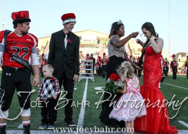 Past Queen Michaela Johnson helps 2016 Queen Kate Warren with her sash during the Homecoming Festivities prior to the game. The Great Bend Panthers defeated the Dodge City Demons 34 to 27 at Memorial Stadium in Great Bend, Kansas on September 23, 2016. (Photo: Joey Bahr, www.joeybahr.com)