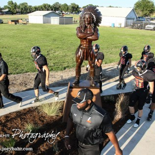 The Larned Indians walk by and touch the base of the new new Indian statue before the start of the game. The Pratt Greenbacks win 31 to 16 over the Larned Indians at Earl Roberts Field in Larned, Kansas on September 2, 2016. (Photo: Joey Bahr, www.joeybahr.com)
