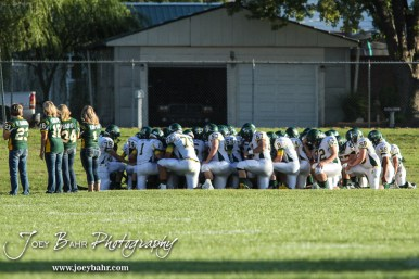 The Pratt Greenbacks kneel in the end zone and pray prior to the game. The Pratt Greenbacks win 31 to 16 over the Larned Indians at Earl Roberts Field in Larned, Kansas on September 2, 2016. (Photo: Joey Bahr, www.joeybahr.com)