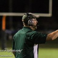 Pratt Greenback Head Coach Jamie Cruce calls in a play from the sideline. The Pratt Greenbacks win 31 to 16 over the Larned Indians at Earl Roberts Field in Larned, Kansas on September 2, 2016. (Photo: Joey Bahr, www.joeybahr.com)
