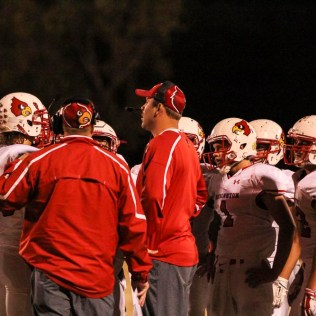Hoisington Cardinal Head Coach Zach Baird talks to his players during a timeout. The Hoisington Cardinals defeated the Ellsworth Bearcats 39 to 20 at Shanelac Field in Ellsworth, Kansas on October 14, 2016. (Photo: Joey Bahr, www.joeybahr.com)