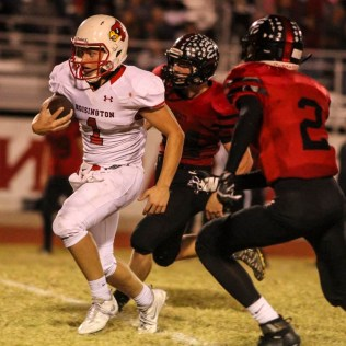 Hoisington Cardinal Tyler Specht (#1) carries the ball as Ellsworth Bearcat Remmington Cravens (#2) closes in. The Hoisington Cardinals defeated the Ellsworth Bearcats 39 to 20 at Shanelac Field in Ellsworth, Kansas on October 14, 2016. (Photo: Joey Bahr, www.joeybahr.com)