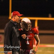 Hoisington Cardinal Head Coach Zach Baird gives the next play to Tyler Specht (#1). The Hoisington Cardinals defeated the Lyons Lions to win the KSHSAA Class 3A District 15 Championship at Elton Brown Field in Hoisington, Kansas on October 27, 2016. (Photo: Joey Bahr, www.joeybahr.com)