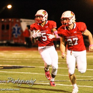 Hoisington Cardinal Hunter Hanzlick (#27) lead blocks for Cameron Davis (#5). The Hoisington Cardinals defeated the Lyons Lions to win the KSHSAA Class 3A District 15 Championship at Elton Brown Field in Hoisington, Kansas on October 27, 2016. (Photo: Joey Bahr, www.joeybahr.com)