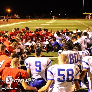 Both teams gather to pray following the game in memory of John Breit. The Hoisington Cardinals defeated the Lyons Lions to win the KSHSAA Class 3A District 15 Championship at Elton Brown Field in Hoisington, Kansas on October 27, 2016. (Photo: Joey Bahr, www.joeybahr.com)