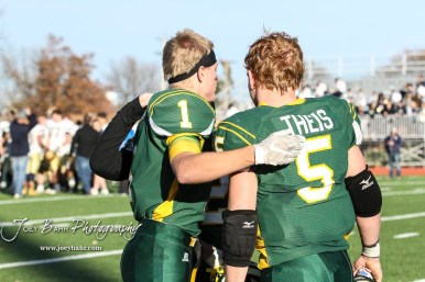 Pratt Greenbacks Hunter Kaufman (#1) and Travis Theis (#5) who both scored in the game embrace while waiting for the Championship trophy. The Pratt Greenbacks defeated the Hayden Wildcats 48 to 14 to win the KSHSAA Class 4A Division II State Championship Game at Salina Stadium in Salina, Kansas on November 26, 2016. (Photo: Joey Bahr, www.joeybahr.com)