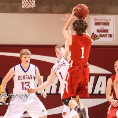 Otis-Bison Cougar #1 Blake Bahr tries to block a shot taken by Hoisington Cardinal #1 Brenner Donovan. The Hoisington Cardinals defeated Otis-Bison Cougars 56 to 39 in the Boys Semi-Final of the 2017 Hoisington Winter Jam at Hoisington Activity Center in Hoisington, Kansas on January 20, 2017. (Photo: Joey Bahr, www.joeybahr.com)