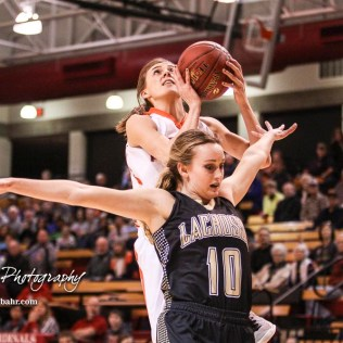LaCrosse Lady Leopard #10 Kacee Klozenbucher tries to block Otis-Bison Lady Cougar #10 Taylor Regan from going for a layup. The Otis-Bison Lady Cougars defeated the LaCrosse Lady Leopards 61 to 55 in the Girls Semi-Final of the 2017 Hoisington Winter Jam at Hoisington Activity Center in Hoisington, Kansas on January 20, 2017. (Photo: Joey Bahr, www.joeybahr.com)