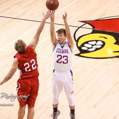 Hoisington Cardinal #22 Grant Dolechek tips a shot from Otis-Bison Cougar #23 Maitland Wiltse. The Hoisington Cardinals defeated Otis-Bison Cougars 56 to 39 in the Boys Semi-Final of the 2017 Hoisington Winter Jam at Hoisington Activity Center in Hoisington, Kansas on January 20, 2017. (Photo: Joey Bahr, www.joeybahr.com)