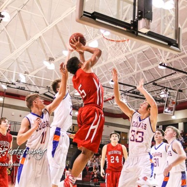 Hoisington Cardinal #5 Cameron Davis goes for a layup as Otis-Bison Cougars #11 Trevor Trapp, #23 Maitland Wiltse, and #33 Anton Foust try to defend. The Hoisington Cardinals defeated Otis-Bison Cougars 56 to 39 in the Boys Semi-Final of the 2017 Hoisington Winter Jam at Hoisington Activity Center in Hoisington, Kansas on January 20, 2017. (Photo: Joey Bahr, www.joeybahr.com)