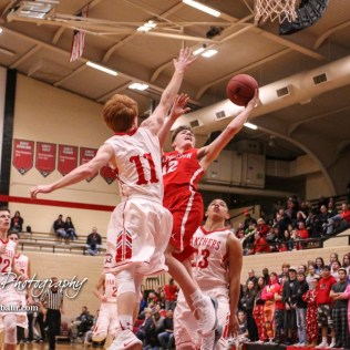 Great Bend Panther #11 Konner Ireland tries to block a shot by McPherson Bullpup #12 Mason Alexander. The McPherson Bullpups defeated the Great Bend Panthers with a score of 57 to 30 at the Great Bend High School Fieldhouse in Great Bend, Kansas on February 7, 2017. (Photo: Joey Bahr, www.joeybahr.com)