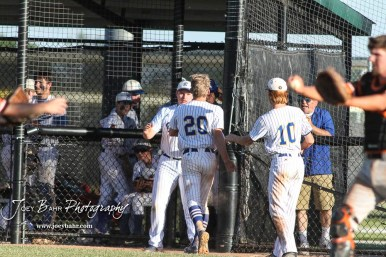 Teammates greet Bluestem Lion #20 Blake Bevan after scoring a run in the top of the fifth inning. The Bluestem Lions defeated the Ellis Railroaders 8 to 5 in the KSHSAA Class 2-1A State Baseball Championship game at Great Bend Sports Complex in Great Bend, Kansas on May 26, 2017. (Photo: Joey Bahr, www.joeybahr.com)