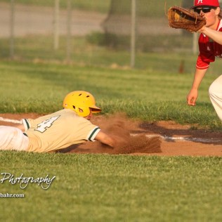 Pratt Greenback #4 Landen Studer dives back to first as Hoisington Cardinal #8 Hunter Hanzlick prepares to catch the ball and try to tag out the runner in the top of the fifth inning. The Pratt Greenbacks defeated the Hoisington Cardinals 12 to 0 at Bicentennial Park in Hoisington, Kansas on May 9, 2017. (Photo: Joey Bahr, www.joeybahr.com)