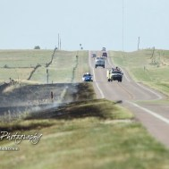 Two trucks from the Galatia Fire Department arrive on the scene of the fire as a Barton County Sheriff helps with traffic flow on US Highway 281. Members of the Olmitz, Hoisington, and Galatia Fire Departments respond to a controlled burn that got out of control two miles north of the junction of Kansas Highway 4 and US Highway 281 near Hoisington, Kansas on July 1, 2017. (Photo: Joey Bahr, www.joeybahr.com)