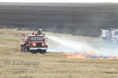 A Hoisington Fire Department firefighter sprays down burning stubble. Members of the Olmitz, Hoisington, and Galatia Fire Departments respond to a controlled burn that got out of control two miles north of the junction of Kansas Highway 4 and US Highway 281 near Hoisington, Kansas on July 1, 2017. (Photo: Joey Bahr, www.joeybahr.com)