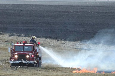 A firefighter sprays down flames from burning wheat stubble. Members of the Olmitz, Hoisington, and Galatia Fire Departments respond to a controlled burn that got out of control two miles north of the junction of Kansas Highway 4 and US Highway 281 near Hoisington, Kansas on July 1, 2017. (Photo: Joey Bahr, www.joeybahr.com)