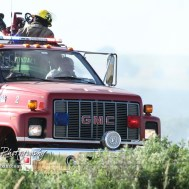 Firefighters discuss where to attack next as they search for hotspots. Members of the Olmitz, Hoisington, and Galatia Fire Departments respond to a controlled burn that got out of control two miles north of the junction of Kansas Highway 4 and US Highway 281 near Hoisington, Kansas on July 1, 2017. (Photo: Joey Bahr, www.joeybahr.com)