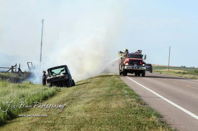A firefighter from the Hoisington Fire Department sprays down a burning part of the ditch alongside US Highway 281. Members of the Olmitz, Hoisington, and Galatia Fire Departments respond to a controlled burn that got out of control two miles north of the junction of Kansas Highway 4 and US Highway 281 near Hoisington, Kansas on July 1, 2017. (Photo: Joey Bahr, www.joeybahr.com)