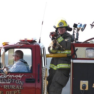 A firefighter with the Hoisington Fire Department stands ready to spray down a hotspot. Members of the Olmitz, Hoisington, and Galatia Fire Departments respond to a controlled burn that got out of control two miles north of the junction of Kansas Highway 4 and US Highway 281 near Hoisington, Kansas on July 1, 2017. (Photo: Joey Bahr, www.joeybahr.com)