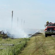 A firefighter with the Hoisington Fire Department extinguishes a fire in the ditch alongside US Highway 281. Members of the Olmitz, Hoisington, and Galatia Fire Departments respond to a controlled burn that got out of control two miles north of the junction of Kansas Highway 4 and US Highway 281 near Hoisington, Kansas on July 1, 2017. (Photo: Joey Bahr, www.joeybahr.com)