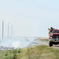 A truck with the Hoisington Fire Department pulls out onto US Highway 281 to spray down flames in the ditch. Members of the Olmitz, Hoisington, and Galatia Fire Departments respond to a controlled burn that got out of control two miles north of the junction of Kansas Highway 4 and US Highway 281 near Hoisington, Kansas on July 1, 2017. (Photo: Joey Bahr, www.joeybahr.com)
