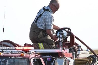 Mike Riese of the Hoisington Fire Department works on unrolling a hose to fight a burning wood pile. Members of the Olmitz, Hoisington, and Galatia Fire Departments respond to a controlled burn that got out of control two miles north of the junction of Kansas Highway 4 and US Highway 281 near Hoisington, Kansas on July 1, 2017. (Photo: Joey Bahr, www.joeybahr.com)