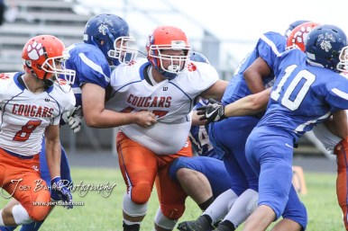 Otis-Bison Cougar #45 Landon Hoopingarner muscles through block of St. John Tiger #68 Trevor Tanner in the first quarter. The Otis-Bison Cougars defeated the St. John Tigers by a score of 58 to 0 at St. John High School in St. John, Kansas on September 1, 2017. (Photo: Joey Bahr, www.joeybahr.com)