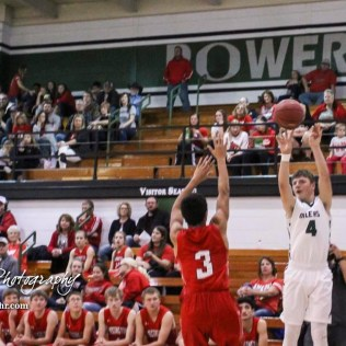 Central Plains Oiler #4 Myles Menges takes a three point shot over Hoisington Cardinal #3 Xavier Robinson. The Central Plains Oilers defeated Hoisington Cardinals by a score of 68 to 24 in a basketball game held at Central Plains High School in Claflin, Kansas on December 1, 2017. (Photo: Joey Bahr, www.joeybahr.com)