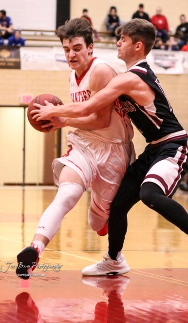 Great Bend Panther #10 Dalton Miller drives down the lan as Buhler Crusader #12 Taiden Hawkinson tries to stop him. The Buhler Crusaders defeated the Great Bend Panthers by a score of 44 to 36 the Great Bend High School Field House in Great Bend, Kansas on January 12, 2018. (Photo: Joey Bahr, www.joeybahr.com)