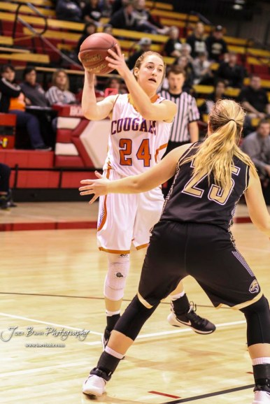 Otis-Bison Lady Cougar #24 Cristen Trapp looks to pass the ball to a teammate as LaCrosse Lady Leopard #25 Addie Kershner defends. The Otis-Bison Lady Cougars defeated the LaCrosse Lady Leopards by a score of 29 to 23 in the Semi-Final of the 2018 Hoisington Winter Jam at the Hoisington Activity Center in Hoisington, Kansas on January 19, 2018. (Photo: Joey Bahr, www.joeybahr.com)