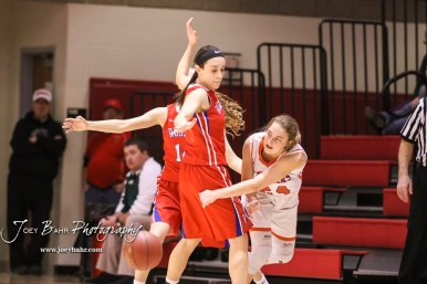 Otis-Bison Lady Cougar #24 Cristen Trapp passes a ball around Russell Lady Bronco #3 Tiffany Dortland. The Russell Lady Broncos defeated the Otis-Bison Lady Cougars by a score of 54 to 34 in the Girls Championship game of the 2018 Hoisington Winter Jam at the Hoisington Activity Center in Hoisington, Kansas on January 20, 2018. (Photo: Joey Bahr, www.joeybahr.com)